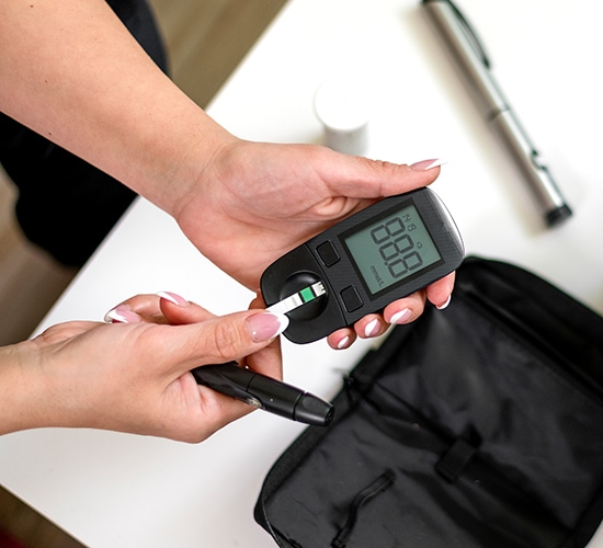 Hands holding blood sugar meter