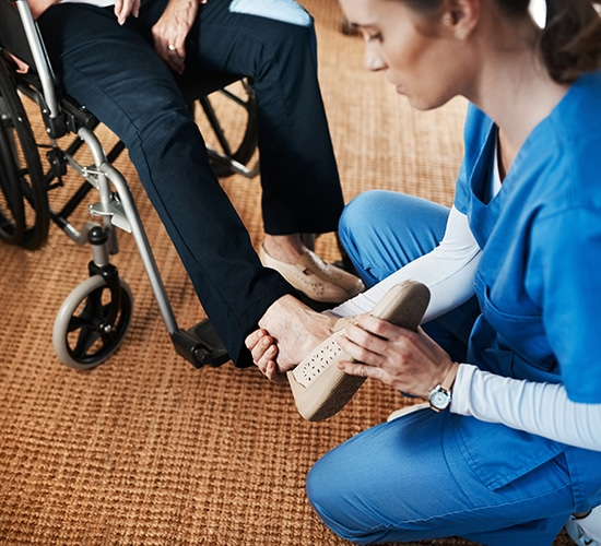 caregiver helping put footwear on a senior patient