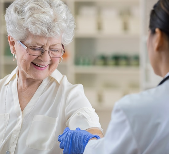 pharmacist applying a bandage to a senior female