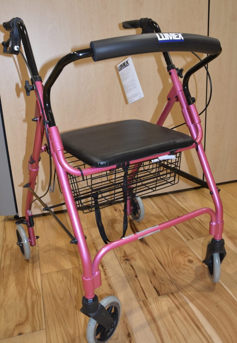 pink colored walker with black seat and handle