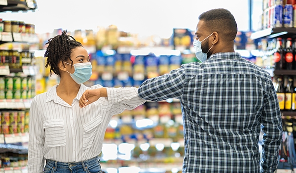how to prevent the flu_man and woman elbow bumping wearing masks